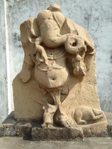 Turbános Ganésa a közép-indiai Rahatgarh Patanból (Sagar District). A táncos lábakból csak a lábfejek maradtak meg a gondosan megfaragott lábujjakkal, de jól látszik a pocakot átkötő kígyózsinór és a patkány-hátasállat. 11-12. század. Sagar City Museum, Sagar, Madhya Pradesh