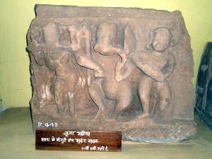 Táncoló Ganésa, a hindi nyelvű felirat szerint banszurín (fuvola) és mridangán (dob) játszó táncosokkal. Madhya Pradesh, 10. század. Dr. Harisingh Gour Archaeological Museum of Sagar University, Sagar (Madhya Pradesh)