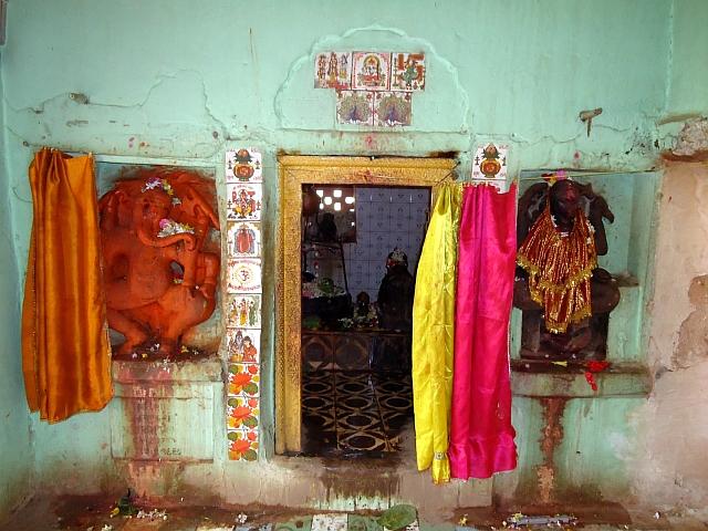 """Narancsvörösre festett táncoló Ganésa a Visnu-Varáha templom egyik mellékszentélye bejáratánál. Régi templom helyén épült újkeletű építmény, de a szobrok többsége eredeti. Madhya Pradesh, Majhauli (Jabalpur District), Kalacsuri-korszak, kb. 11. század. Ganésa mellett a csempéken szerencsejelek sorakoznak. Fentről lefelé haladva 1. bőségkorsó napkereszttel (szvasztika, =""""jó-lét"""", azaz bőség, jószerencse) és szerencsekívánsággal: शुभ लाभ śubh lābh/subh-lábh, =""""boldogságot, hasznot"""", azaz sok szerencsét! 2. Még egy Ganésa, """"Üdv, tisztelet Ganésának!"""" felirattal. 3. Ez Ganésa Ganapatiként. Ganésa és Ganapati ugyanazt jelenti: a ganák, azaz Siva seregének ura. 4. Gájatrí mantra, nagy szentségnek örvendő védikus ima. 5. Nehezen kivehető, de valószínűleg Visnu, Laksmí, Garuda és egy kísérő. 6. Siva a háromágú szigonyával, Párvatíval és Ganésával. 7. Vízililiomok, azaz lótuszok. Az indiai vallásokban a lótusz tisztaság szimbóluma."""